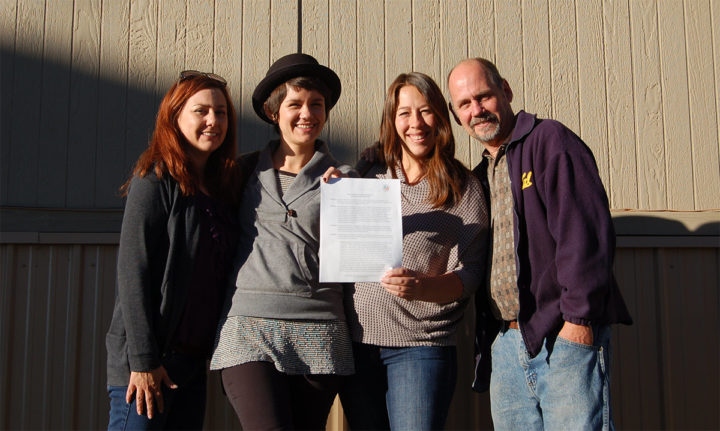 The Pagosa Charter School Initiative (PCSI) board poses outside the ASD administrative offices with a copy of the signed School Board resolution. This founding board will form the core of the yet-to-be-formed Pagosa Peak Open School board of directors.